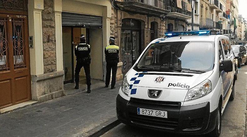 Dos agentes de la Guàrdia Urbana, delante del club cuando fue registrado.