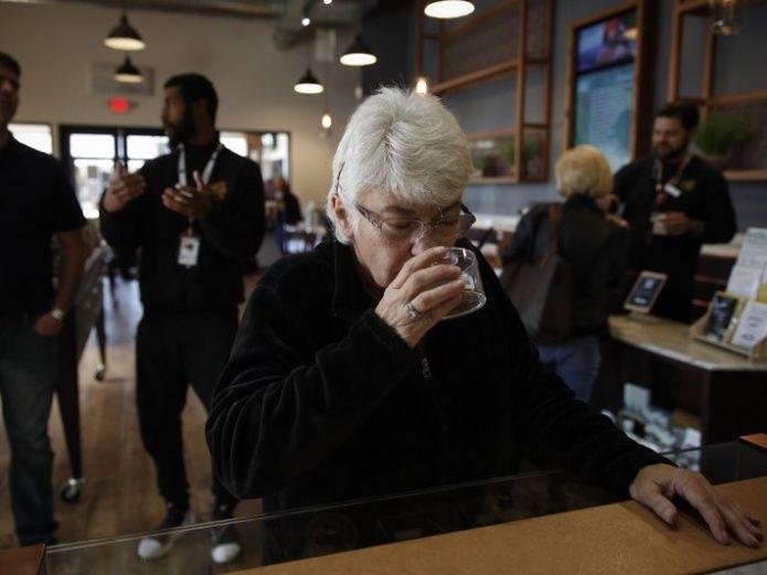 Sandy Sopher, de 65 años, huele un botón de marihuana en el dispensario Bud and Bloom de Santa Ana, California, el 19 de febrero del 2019. Cada vez más ancianos apelan a derivados de la marihuana para tratar problemas médicos en EEUU. (AP Photo/Jae C. Hong)