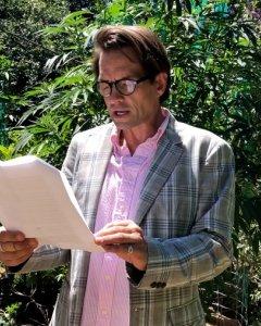 Brent David Fraser, fundador de la Asociación de Ministerios Sacramentales (ASM) y la cual pertenece la Iglesia de las Cien Armonías, posa frente a una planta de marihuana. / Ava Francoeur