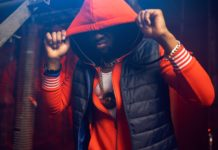 Rapper in red hoodie poses in grunge studio