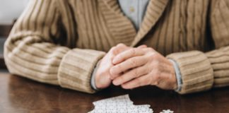 cropped view of senior man playing with puzzles on table