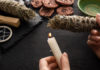 Cropped view of shaman holding candle and smudge stick near witchcraft on black wooden background