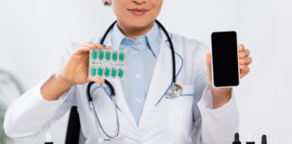 cropped view of african american doctor holding blister pack with capsules and smartphone with blank screen near cbd cubes and bottles