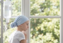 Sad sick child with cancer wearing blue headscarf during treatme