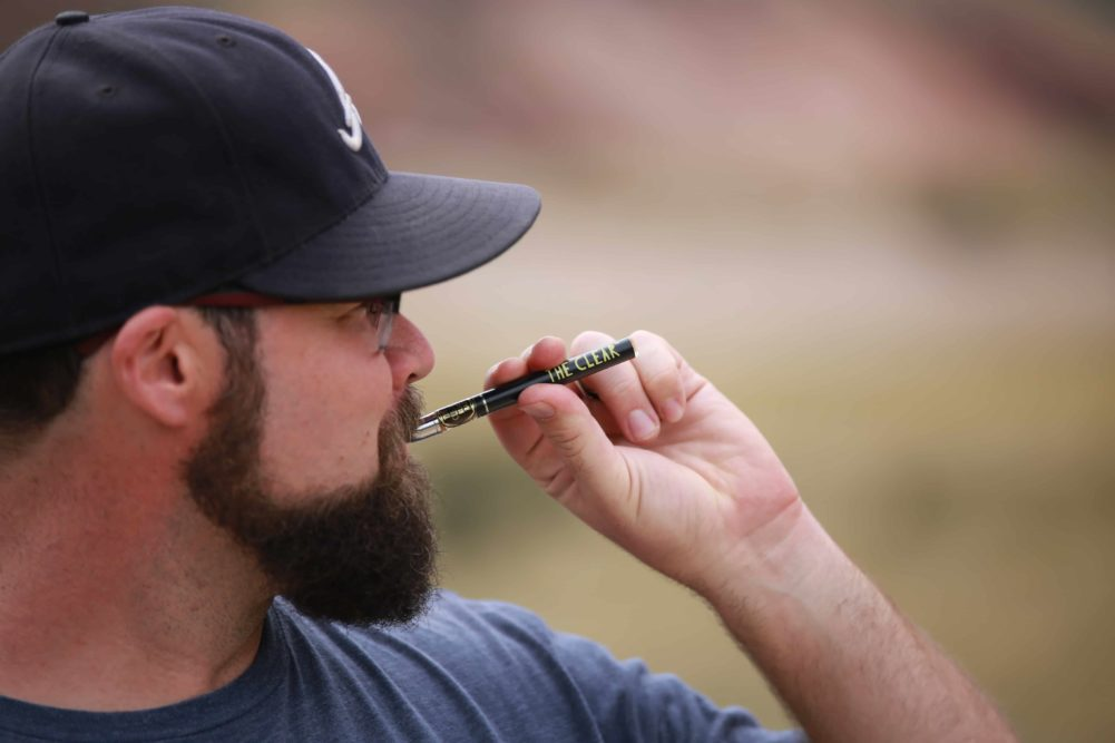 Man in baseball cap with beard pulls The Clear Elite Cartridge while wearing glasses. The Clear Elite is for adult consumption only. Containing the purest, cleanest, most original distillate on the Colorado med and rec market.